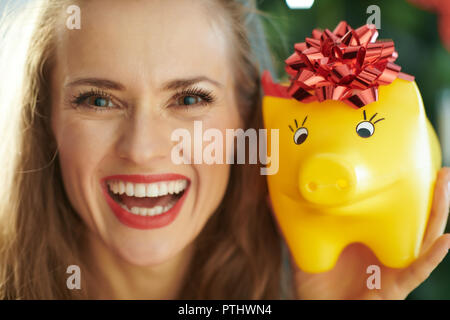 Portrait of happy young woman and yellow piggy bank with red bow near Christmas tree - Stock Image