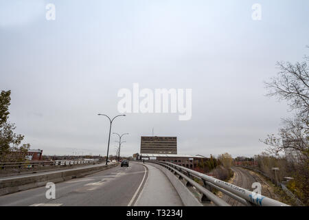 MONTREAL, CANADA - NOVEMBER 9, 2018: North American Highway on Rosemont Boulevard during a cloudy afternoon with cars passing by, an industrial wareho - Stock Image