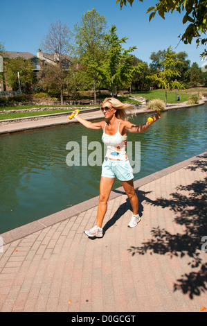 USA, Indiana, Indianapolis, jogger exercising along tree-lined canal in downtown area with architectural features - Stock Image