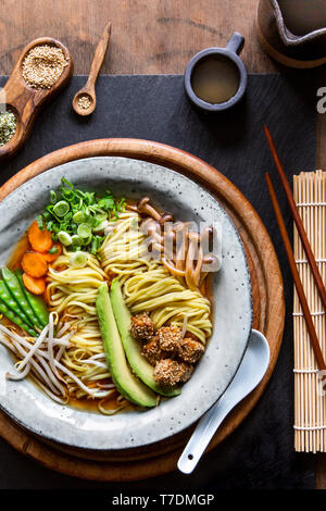 Vegan Japanese Ramen soup with avocado, sesame tofu and mushrooms in grey bowl over wooden background - Stock Image