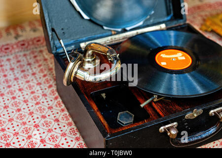 Vintage portable mechanical phonograph with a vinyl record disk. Ancient analog sound technology - Stock Image