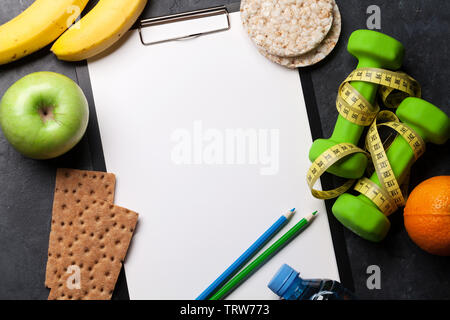 Fitness and healthy food concept. Granola, dumbbells, fruits and drink bottle on stone table. Top view with copy space for your text - Stock Image
