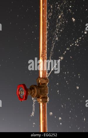 Plumbing burst Leaking Pipe with Tap - Stock Image