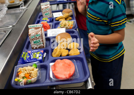 A student makes a selection in an elementary school lunch line. - Stock Image