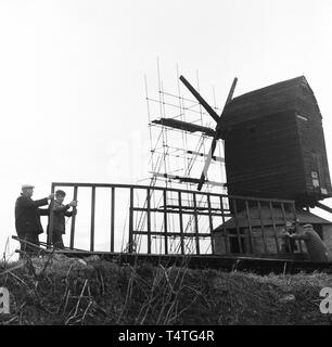 1960s, historical, repairs to the Windmill at Brill, workmen moving one of the original wooden sails. - Stock Image