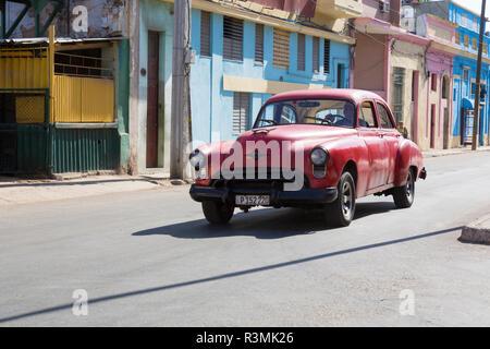 Cuba, Havana. Red classic car passing by painted buildings. Credit as: Wendy Kaveney / Jaynes Gallery / DanitaDelimont.com - Stock Image