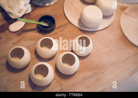 High angle view of ceramics with paint of wooden table at workshop - Stock Image