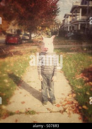 Boy in pig mask on sidewalk - Stock Image