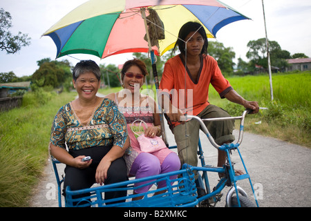 Two Filipinas ride a pedi tricycle taxi in Roxas, Oriental Mindoro, Philippines. - Stock Image