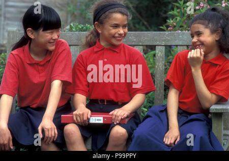 three schoolgirls sitting on bench chatting - Stock Image