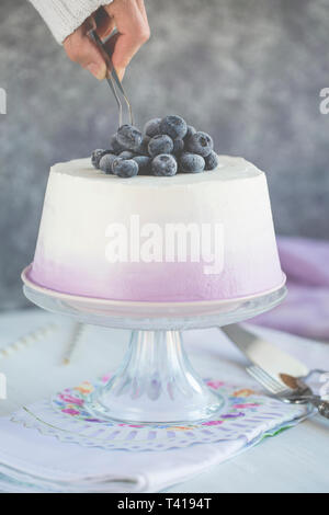 Woman serving a slice of Angel cake with cream and blueberries - Stock Image