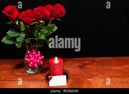 Beautiful red roses in vase with pink bow and red candle with name tag on wooden table on dark background. Valentines, Mothers Day, Easter, Christmas, - Stock Image