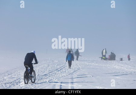 Group of people ice fishing , biking and walking on sea ice at Winter , Finland - Stock Image