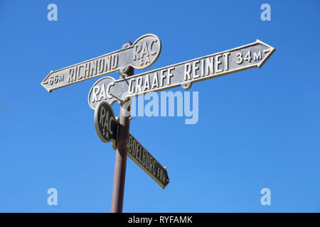From below Arrows at village intersection in Karoo giving directions from Nieu Bethesda, South Africa - March 10, 2019 - Stock Image