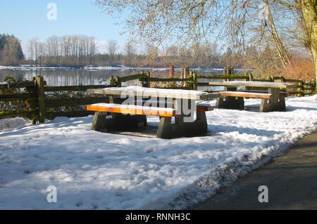 Picnic tables covered in snow. Kanaka Creek Riverfront Regional Park. Maple Ridge, British Columbia, Canada. - Stock Image