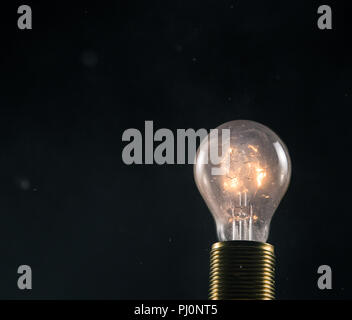 Burning old light bulb on black backround. Concept of new idea and brain storming. - Stock Image