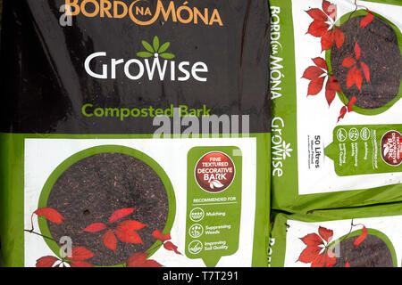 A stack of bags of Composted bark for suppressing weeds and improving soil quality for sale  in a garden centre - Stock Image