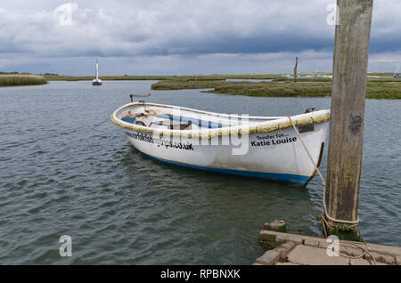A solitary boat moored on a tidal creek at Brancaster Staithe, North Norfolk, UK - Stock Image