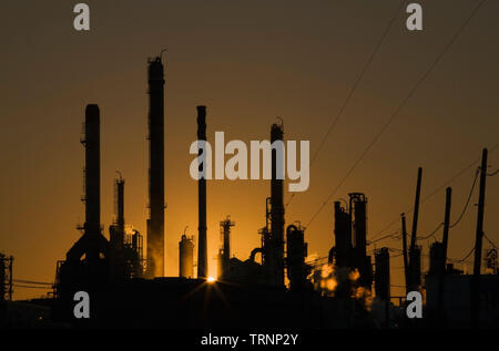 Oil Refinery silhouetted at sunset - Stock Image