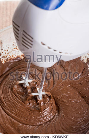 Mixing chocolate cream ganache with hand mixer. - Stock Image