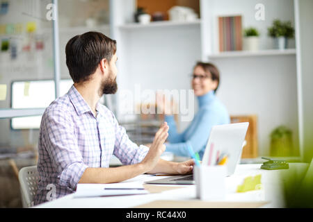 Two office managers sitting by desks and waving by hands to each other while saying something during work - Stock Image