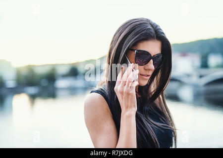Beautiful woman in black dress with sunglasses and smartphone standing by a river in city of Prague, making a phone call. - Stock Image