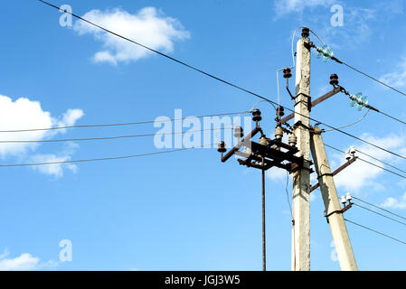 Aged electricity pylon with cables and insulators shot against a blue summer sky with white clouds - Stock Image