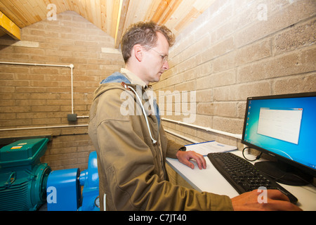 The owner of a small scale hydro electric station at Kilnstones in Longsleddale, Lake District, UK, checks the output - Stock Image