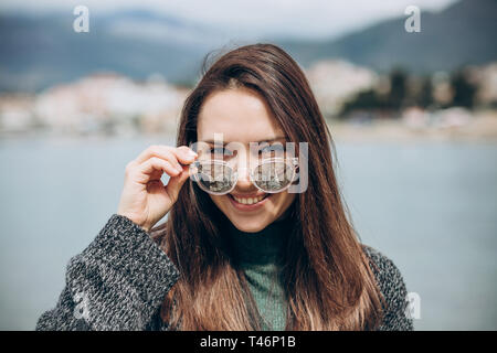 Portrait of a young smiling girl in sunglasses on the background of the sea. - Stock Image