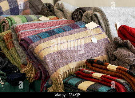 Selection of throws traditionally made of wool in a pile for sale at market traders, great example of crafting industry. - Stock Image