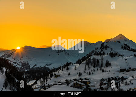 Orange skies and setting sun over the mountains in Obertauern, Austria - Stock Image
