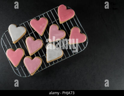 Small Frosted Heart Cookies on Cooling Rack over slate surface - Stock Image