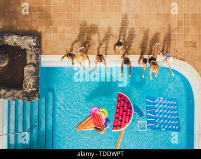People group of young women have fun in summer holiday at the pool playing with coloured trendy inflatable mattress lilo - viewed from high top aerial - Stock Image