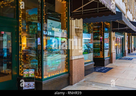 ASHEVILLE, NC, USA-2/16/19: Strings of lights and reflections fom the street shine in realtors' storefront windows along Page St. - Stock Image