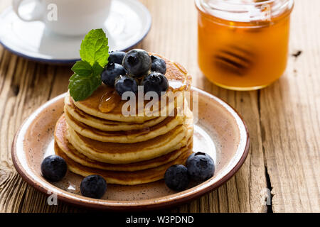 Healthy breakfast or brunch, favorite morning meal. Homemade pancakes, fresh summer berries, coffee and juice on wooden table - Stock Image