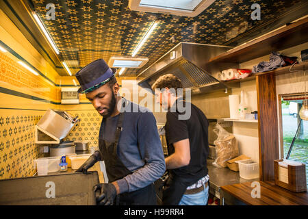 Two men cooking in commercial kitchen of food truck - Stock Image
