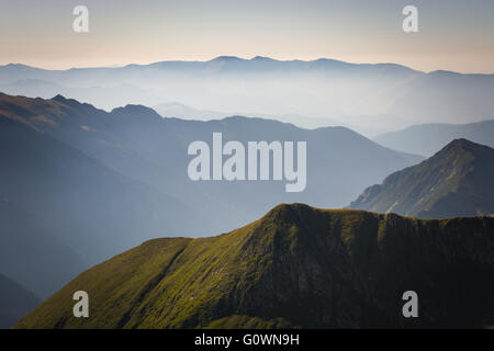 Fog in the mountains, three mountain ranges with a blue sky on the horizon - Stock Image