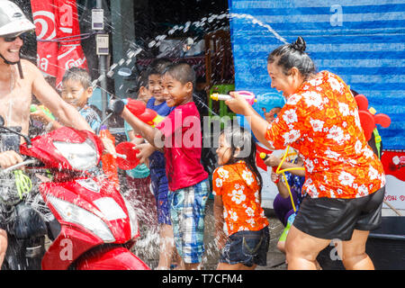 Phuket, Thailand - 13th April 2017: People on a motorbike drenched by Songkran participants. This is how Thais celebrate their new year. - Stock Image
