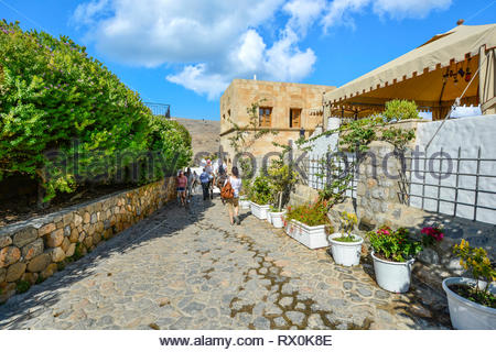 Tourists and donkeys carrying tourists walk a narrow stone path near Lindos on the island of Rhodes, Greece. - Stock Image