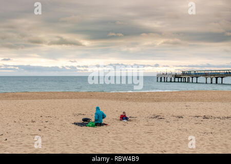Bournemouth, Dorset, UK. 12th January 2019. Sitting on the beach, despite the cold weather in Bournemouth. Credit: Thomas Faull/Alamy Live News - Stock Image