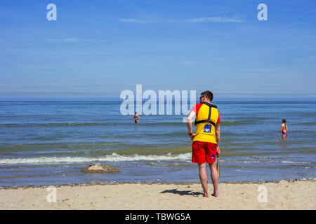 Beach lifeguard supervising bathers at seaside resort along the Belgian North Sea coast, Belgium - Stock Image
