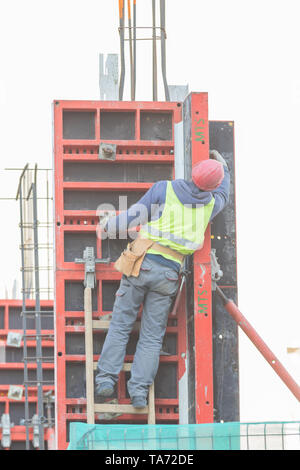 An engineer is climbing up the stairs at the constraction site wearing uniform and helmet. - Stock Image