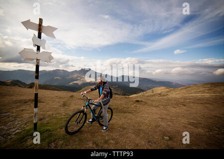 Cyclist on bicycle looking at sign board against cloudy sky - Stock Image