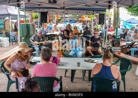 People listen to a band playing live music at the Nightcliff Market in Darwin, Australia. - Stock Image