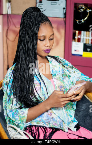 Young woman looking at her mails in her mobile phone. - Stock Image
