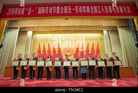 Beijing, China. 23rd Apr, 2019. Representatives pose for a group photo at a conference held to highlight the contribution of 'model workers' and groups in Beijing, capital of China, April 23, 2019. China on Tuesday held a conference here to highlight the contribution of 'model workers' and groups ahead of the International Labor Day, which falls on May 1. A total of 695 individuals and more than 800 groups were honored at the event. Credit: Cai Yang/Xinhua/Alamy Live News - Stock Image