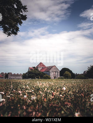 An old English church surrounded by fields with blue sky and white clouds - Stock Image