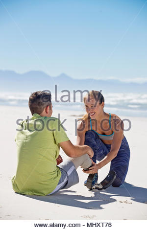 Woman Helping Man To Attach Prosthetic Blade Before Exercising On Beach Together - Stock Image