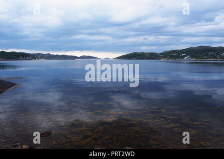 A view out of Lochinver, Scotland over to the harbour and out to the open  sea with seaweed covered immersed stones in the foreground - Stock Image