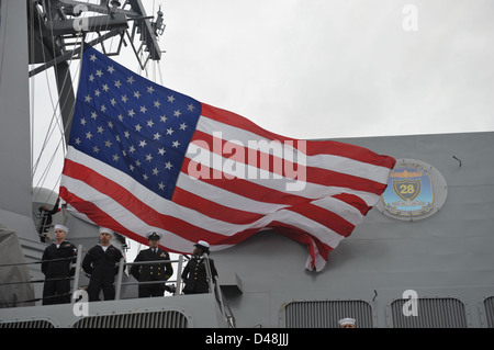 Sailors lower the American flag aboard USS Forrest Sherman. - Stock Image